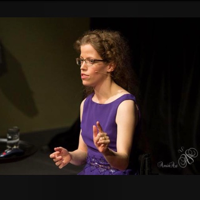Grace Quantock in a purple dress, speaking on stage at TEDx Aylesbury