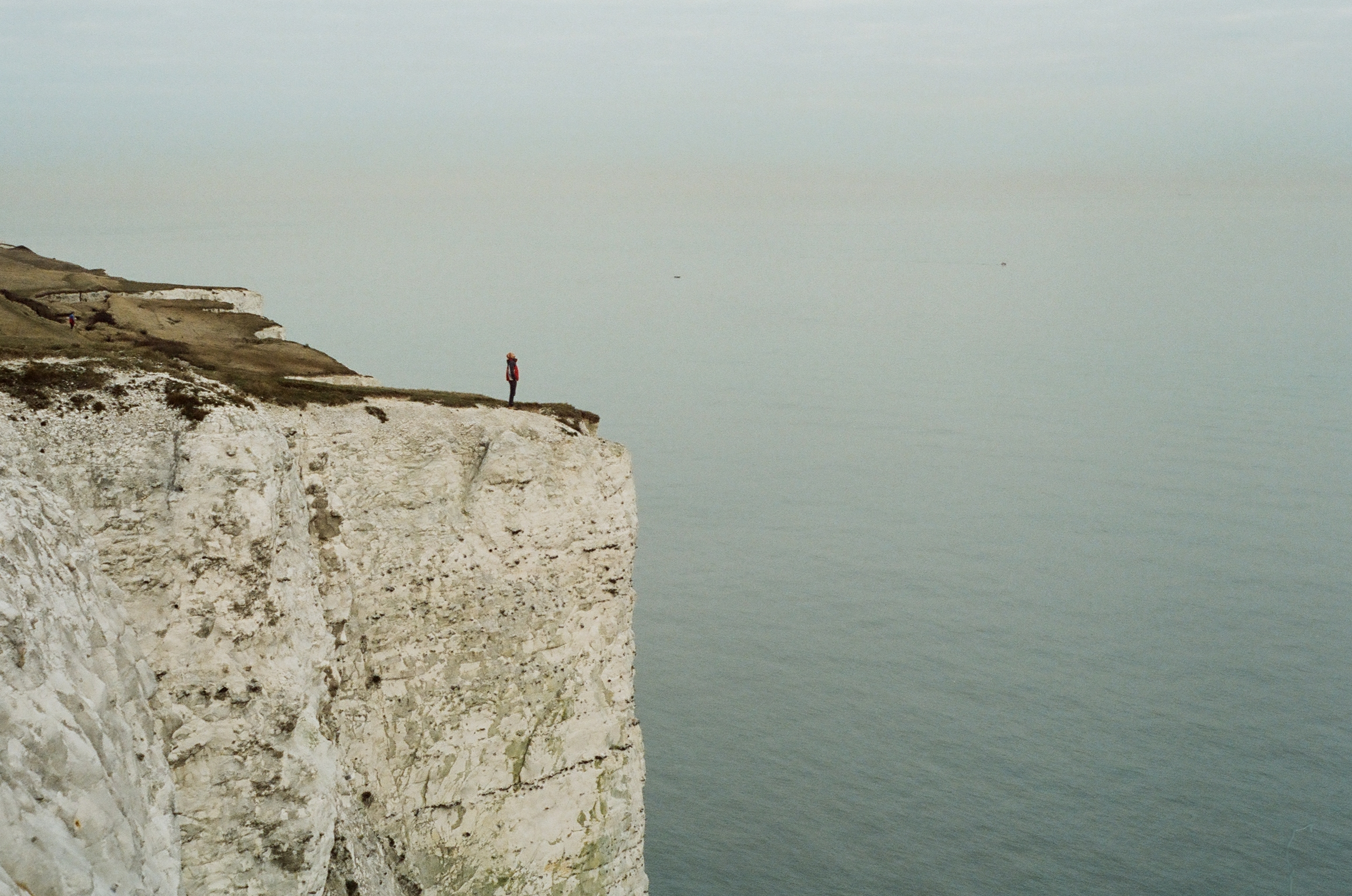 long shot of a person standing on the edge of a cliff surrounded by water