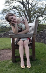 Grace Quantock sitting on a bench with head tilted & resting in hand