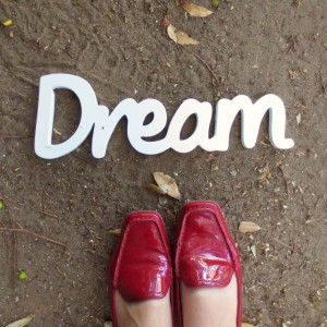 The word Dream in white on the dirt ground with red shoes below