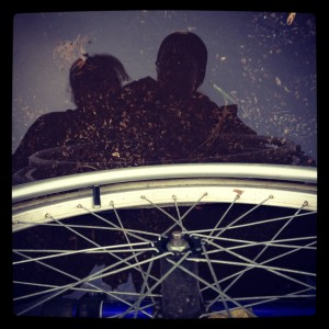 Reflections of Grace & Linus in water with wheelchair wheel