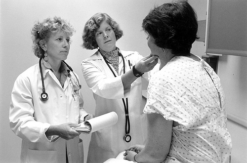 two female doctors examining a female patient