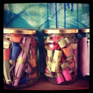 mason jars filled with rolled up papers tied with ribbon of date night ideas