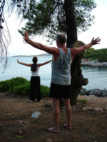 People with their backs to us practicing Qi Gong near the water