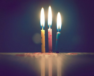 3 birthday candles burning on a table