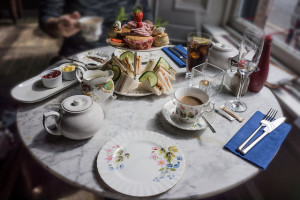 tea party at home - teapot, saucers, plates, sandwiches, sweets set up on round table