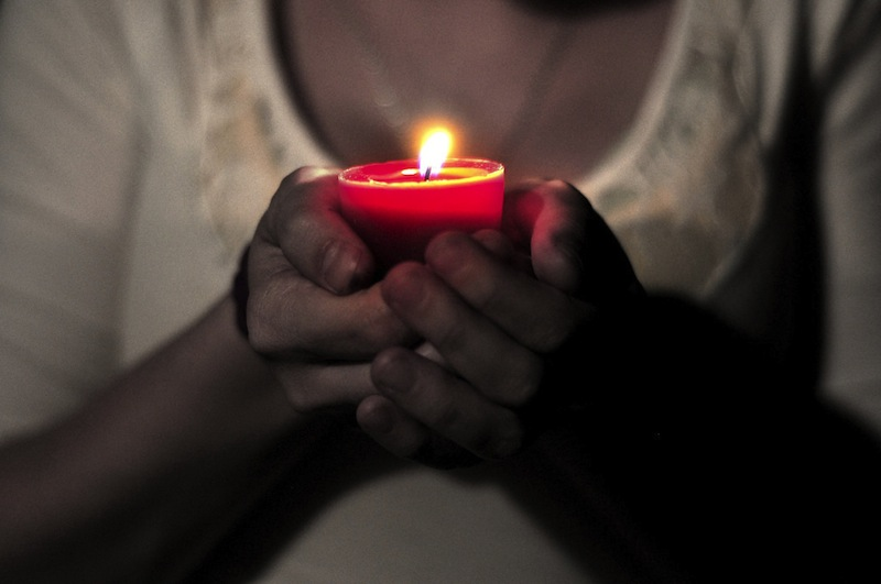 Person holding a candle - 7 Gentle, Generous, Restorative Ways to Feel Better