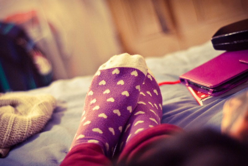 Socked feet on bed - 7 Gentle, Generous, Restorative Ways to Feel Better