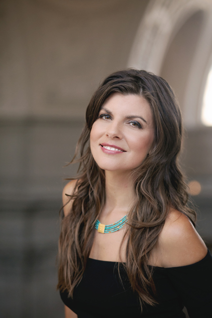 KC Baker in turquoise and gold necklace and black dress in front of a stone archway - Trailblazer Interview: KC Baker & Public Speaking Skills to Transform Your Self & World
