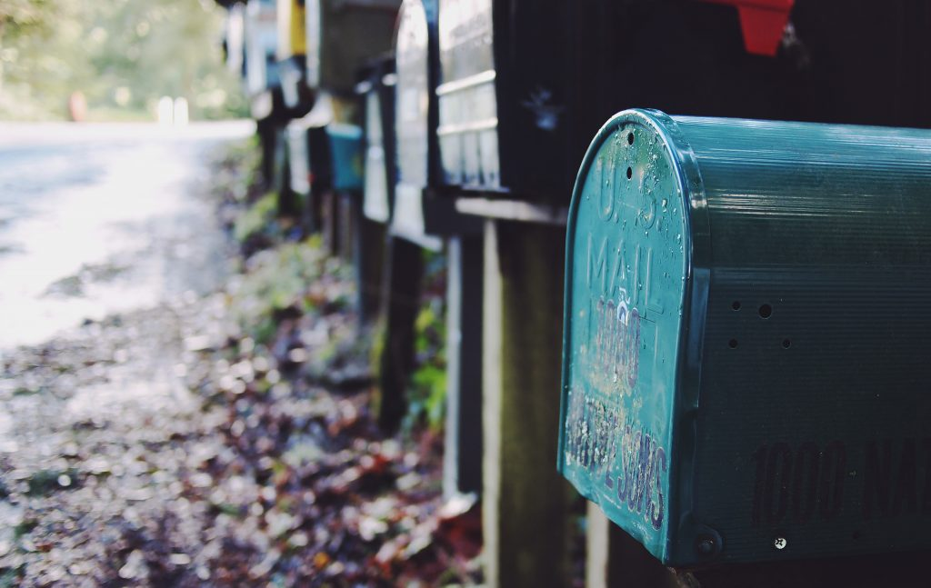 teal mailbox in a row, leaves on the road