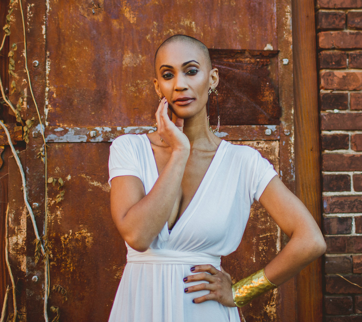 L'Erin Alta standing against a wall wearing a white dress and gold bangle