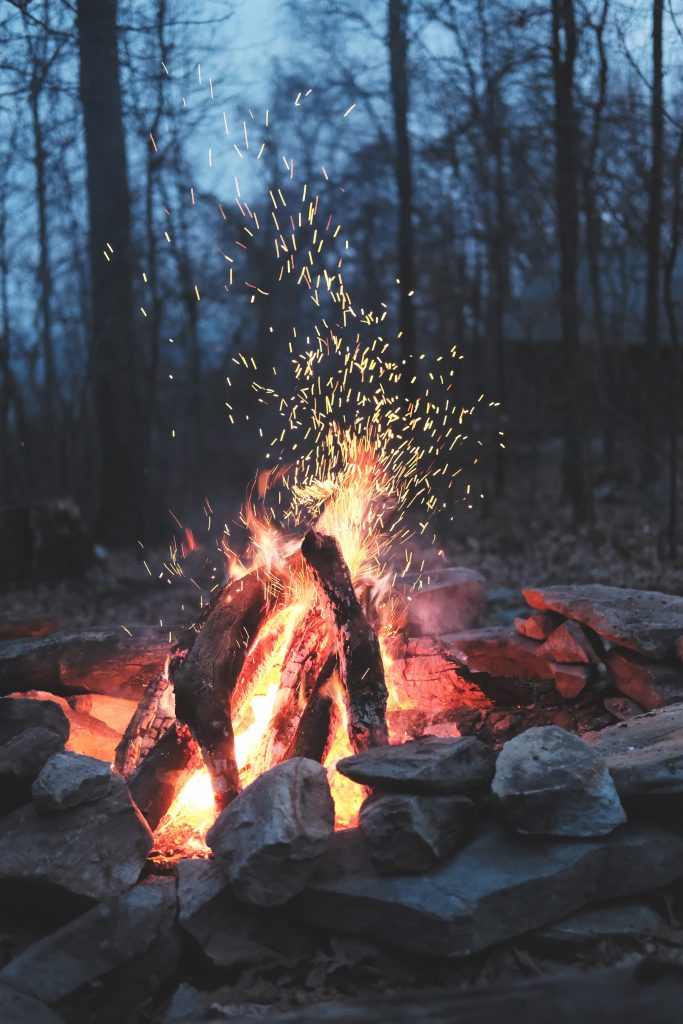 Photo of a fire pit with lit fire in woods shooting sparks