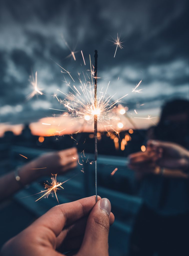 hands holding sparklers against a cloudy, low light urban landscape