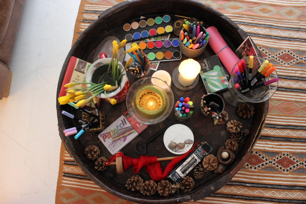 table of art materials and candles shot from above