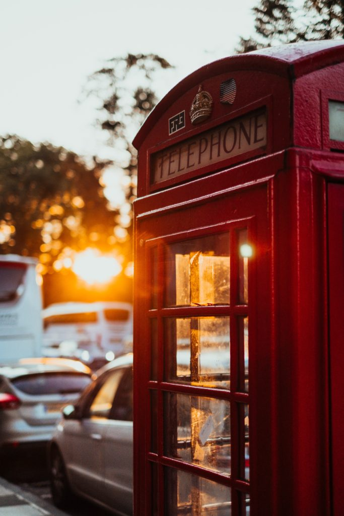 Photograph of red phone box in the sunlight.