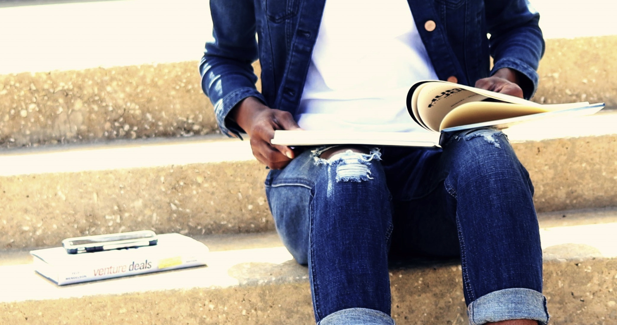 Person sitting on steps, holding an open book, photographed from chest down, wearing denim jeans and jacket.
