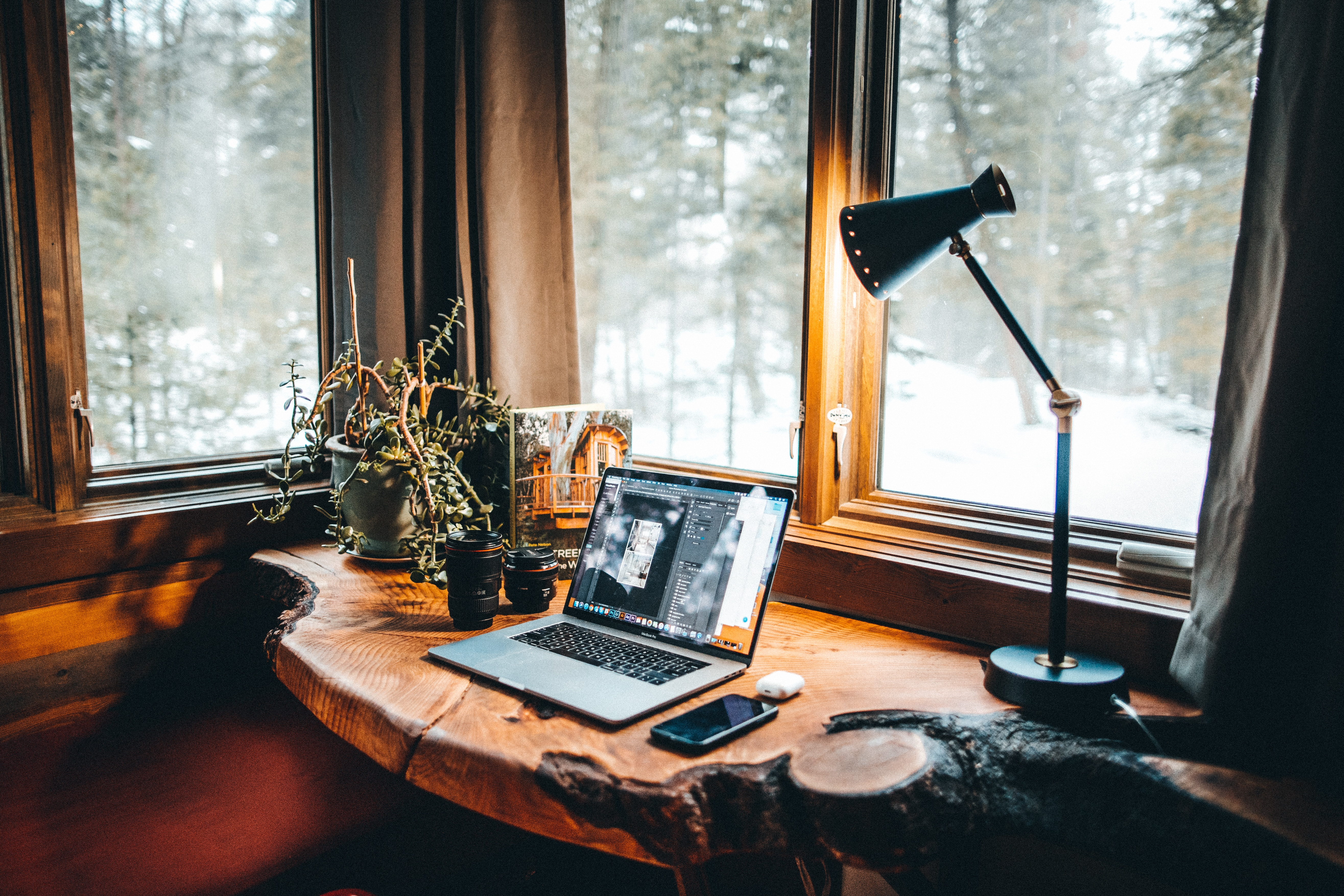 a laptop by a window, snow outside