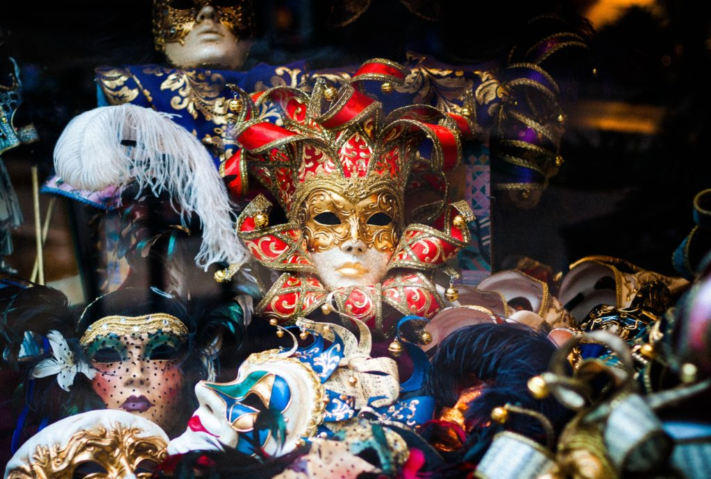 A pile of masks, colourful masks with flowers and feathers