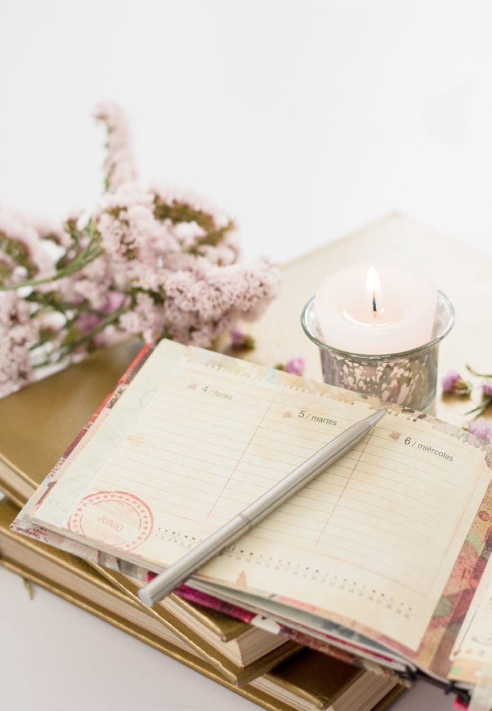 journal open next to lit candle and pink flowers on a table