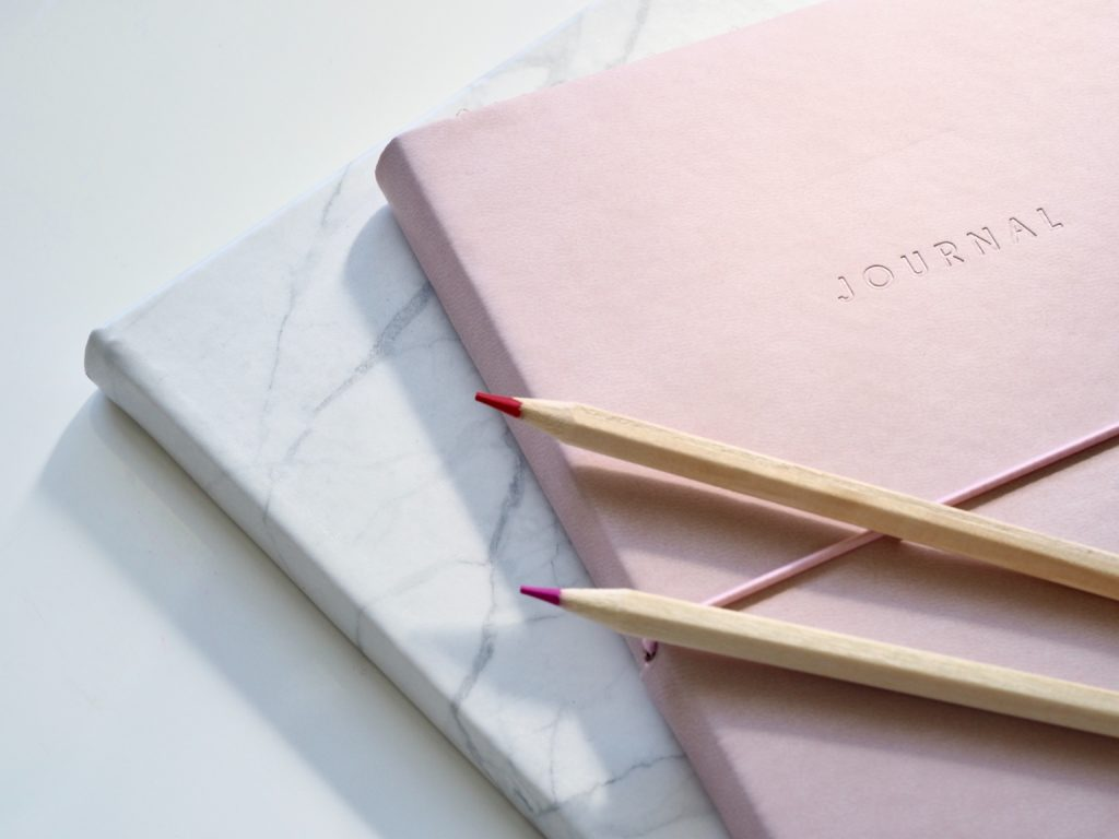 Pile of pink and white marbled journals with a pink pen