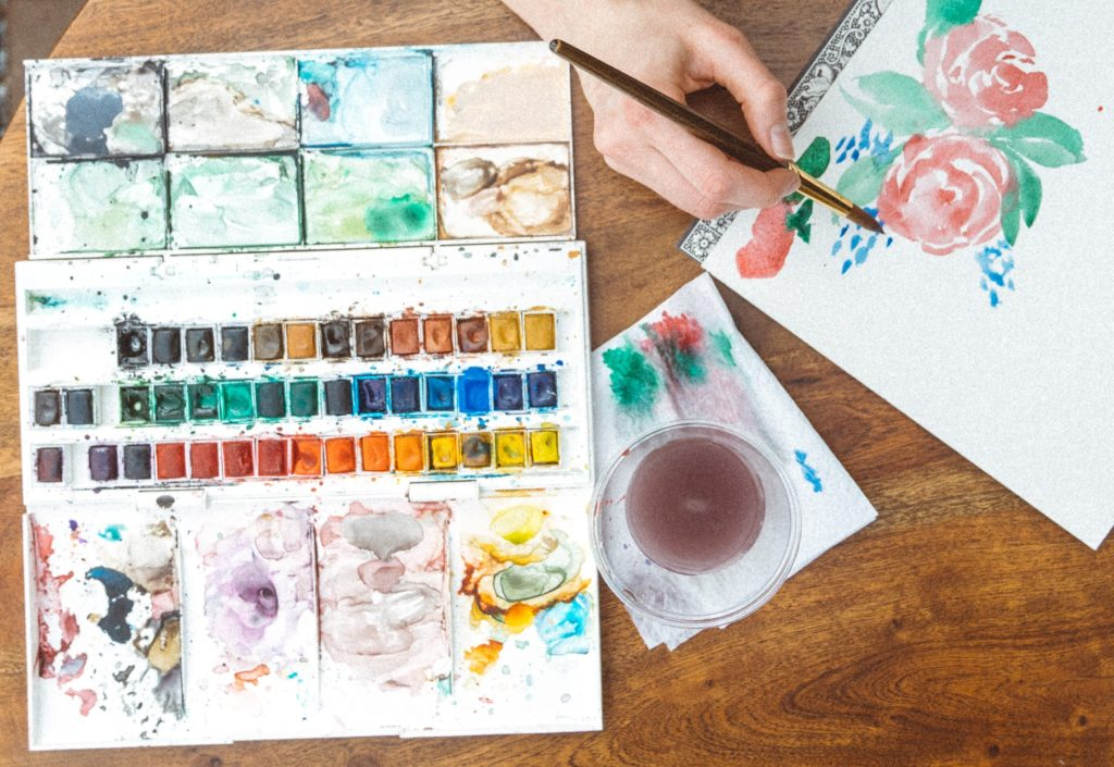 Person painting roses on a blank book with a watercolour palette of paints open on the table
