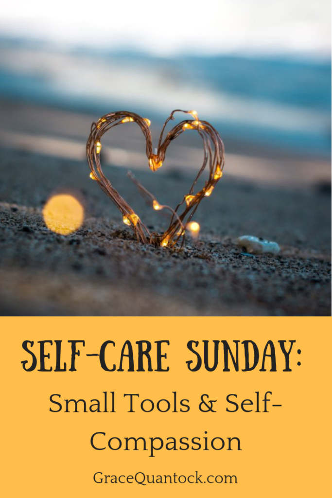 Tiny heart of fairy lights on a beach, stuck in sand and text: Self-Care Sunday: Small Tools & Self-Compassion