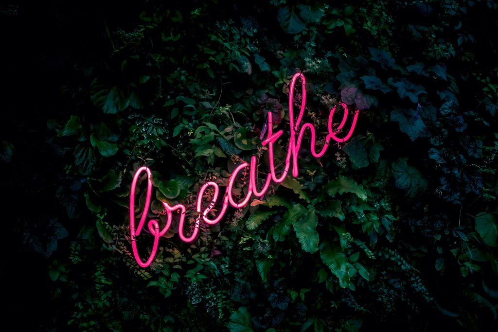 Neon sign 'breathe' over greenery