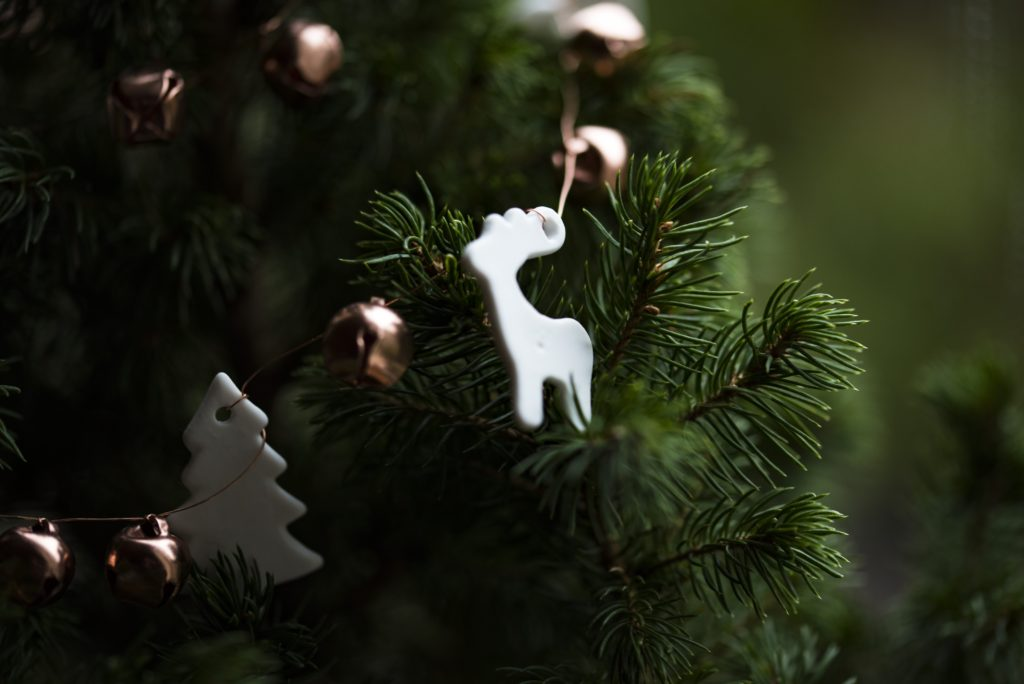 Close up of reindeer ornament on pine Christmas tree