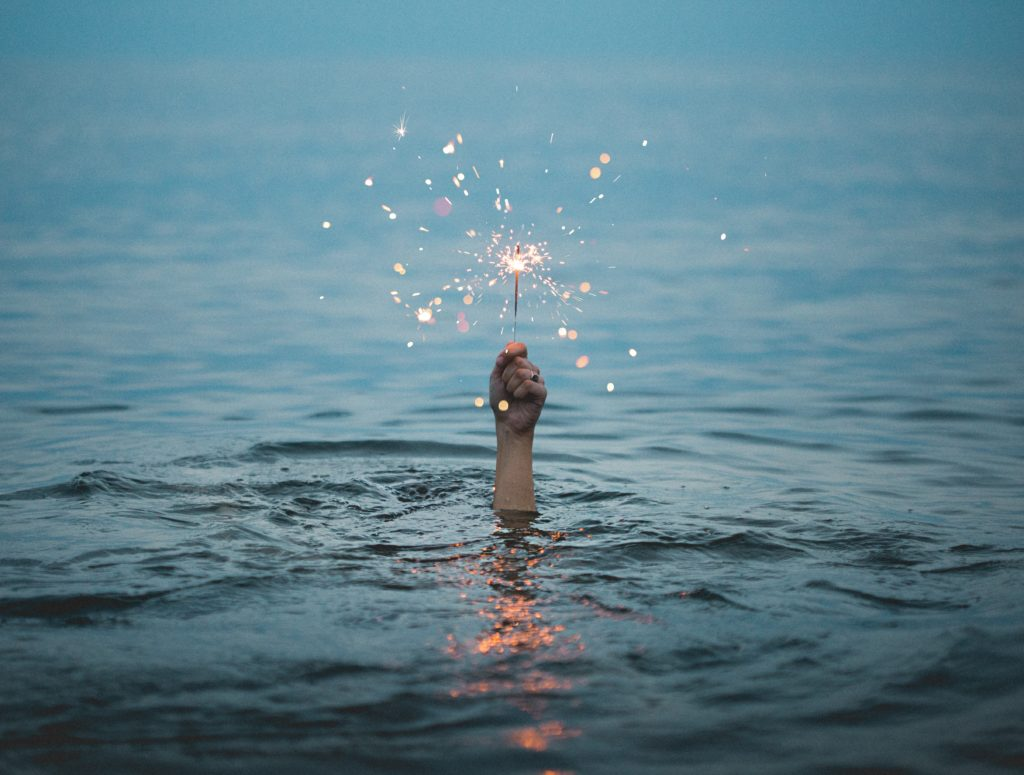 Person under water holding sparkler above it