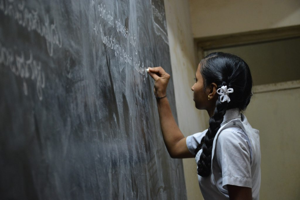 A woman writing on a blackboard with a flower in her hair