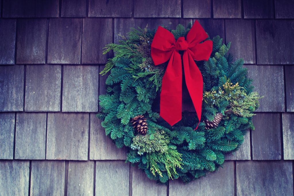 Pine wreath on shingles with a big red ribbon