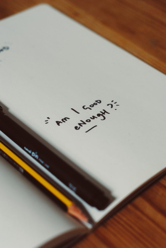 page with 'am I good enough' written on it in black felt tip