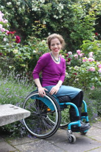 Grace sitting in her wheelchair wearing a teal dress and a pink jumper, roses are growing in the ground behind her.