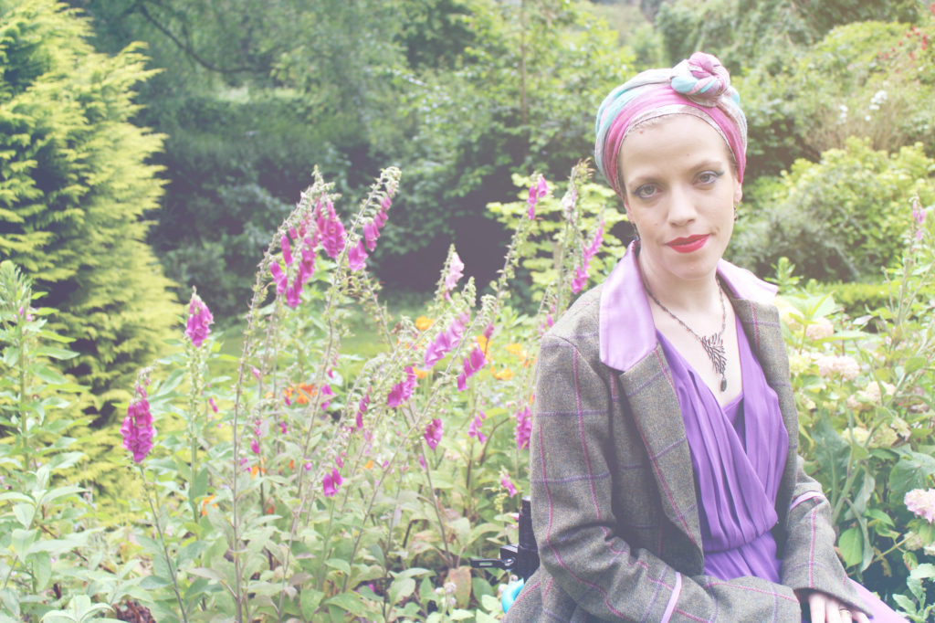 Grace,wearing a head wrap and a tweed jacket, seated, foxgloves behind her.