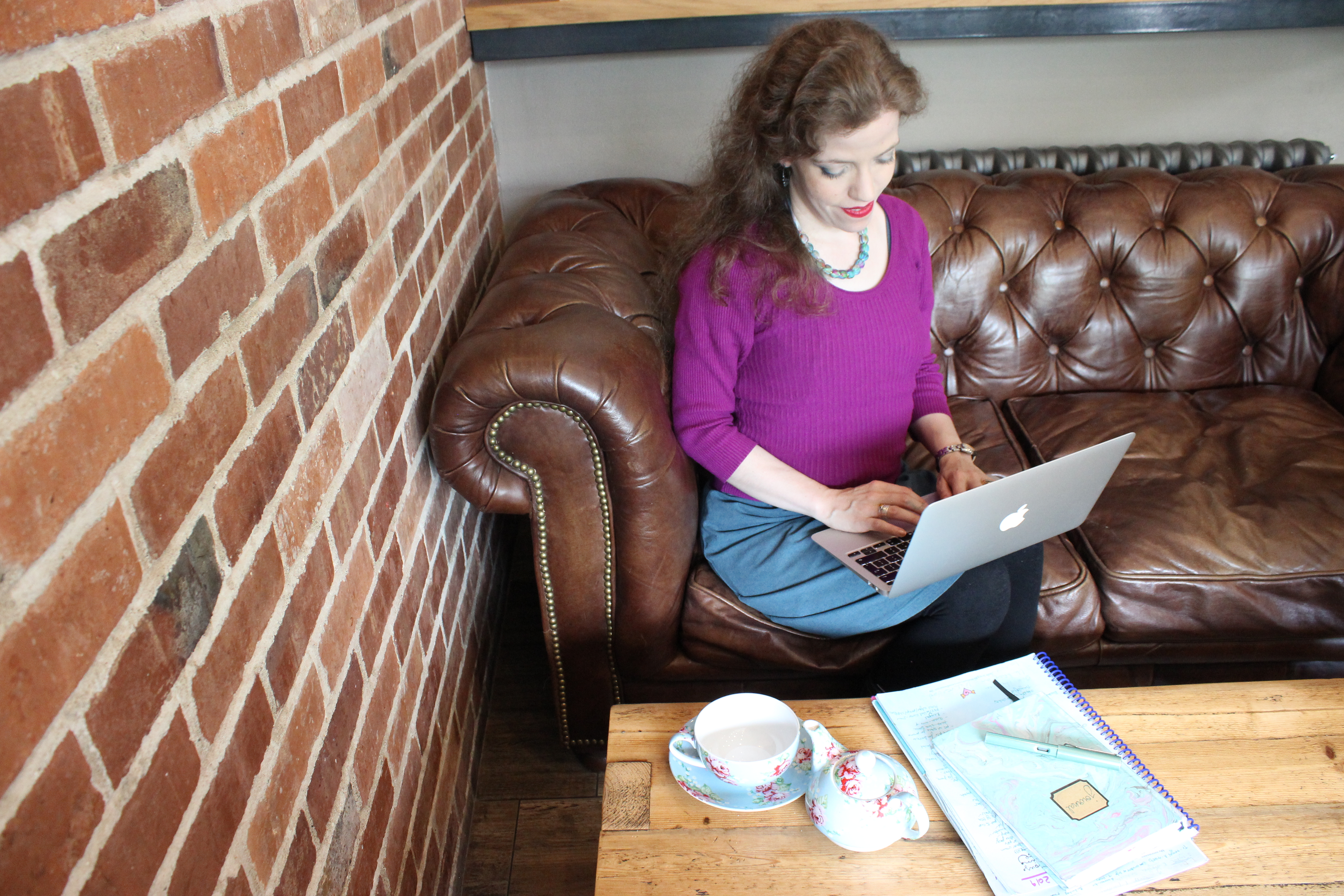 Grace sitting in a cafe, on a soft, typing on a macbook laptop