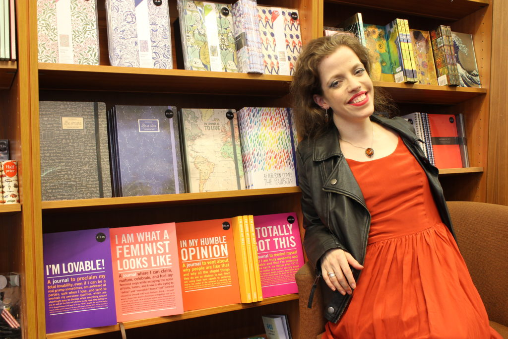 Grace sitting in a bookshop, wearing an orange dress and black jacket