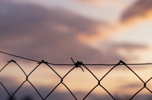 Wire fence against a cloudy sky with sunset behind