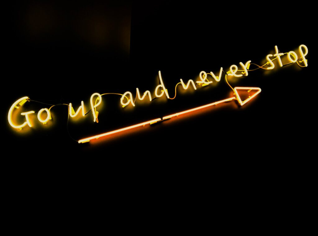 A yellow neon sign saying 'Go up and never stop' with an arrow beneath. Against a black background.