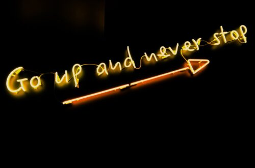Go up and never stop neon letters with arrow on black wall