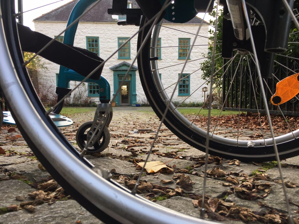 Large white house with teal door seen through Grace's wheelchair wheels. Leaves on the ground under the chair.