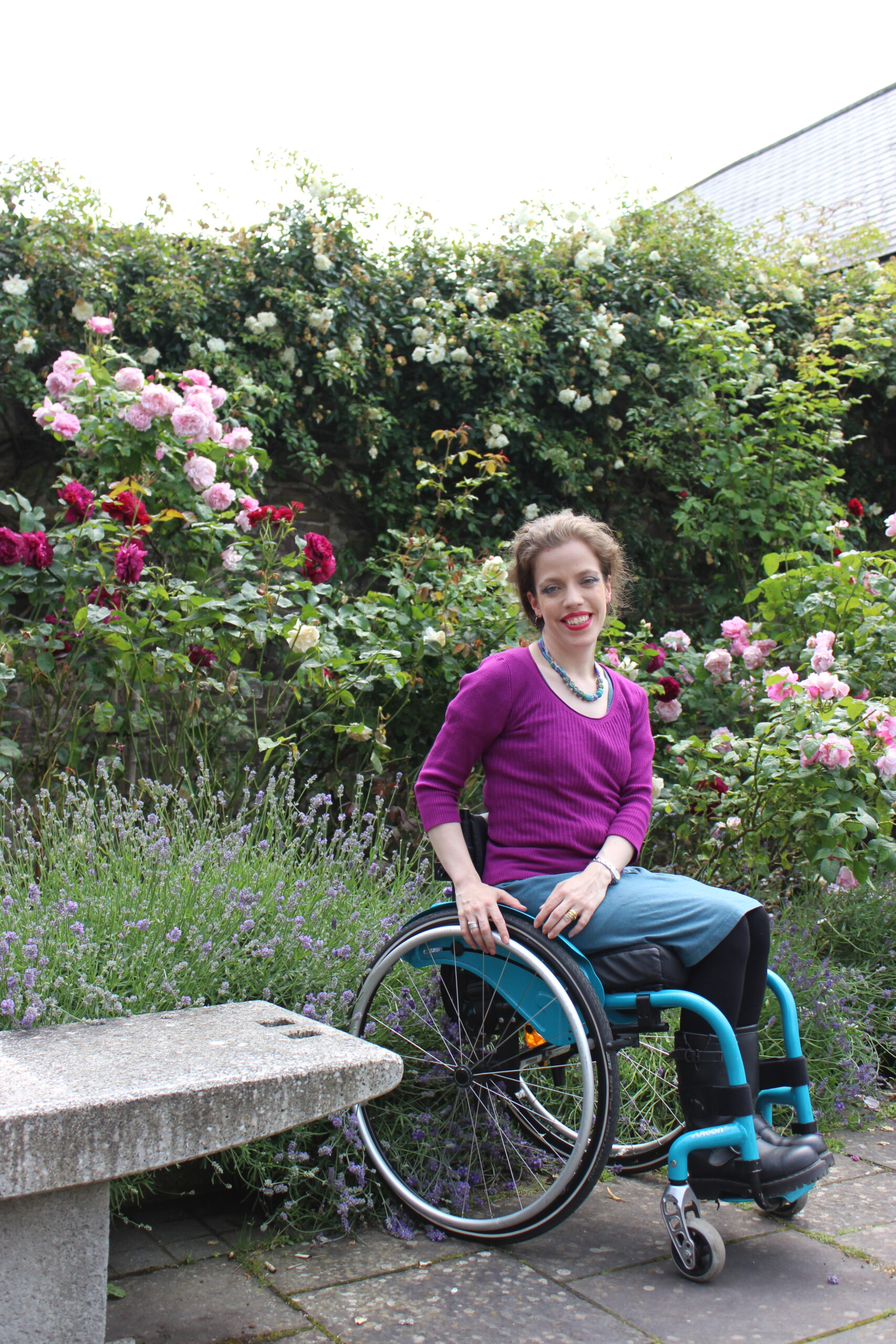 Grace sitting in her teal wheelchair in front of roses in bloom wearing a pink jumper and a teal skirt.